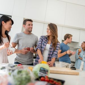 Group of multi-ethnic friends living together and cooking at home in the kitchen