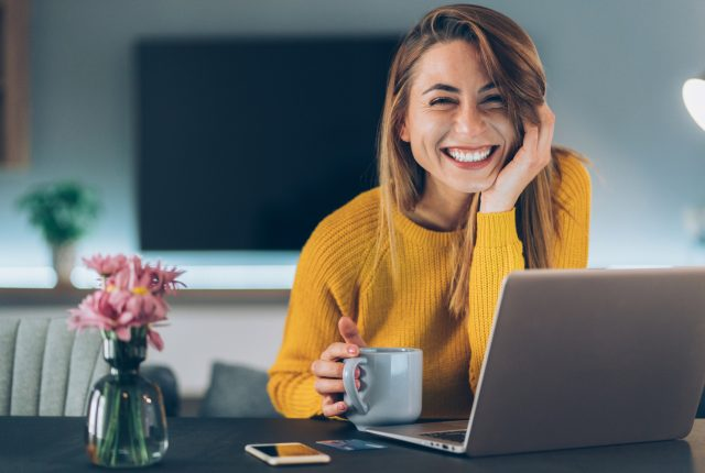 Young blonde beautiful woman drinking coffee, using smartphone and laptop, smiling and looking at camera