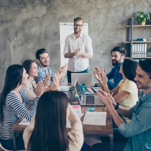 Gret job! Successful business team is clapping their hands in modern workstation, celebrating the performance of new product